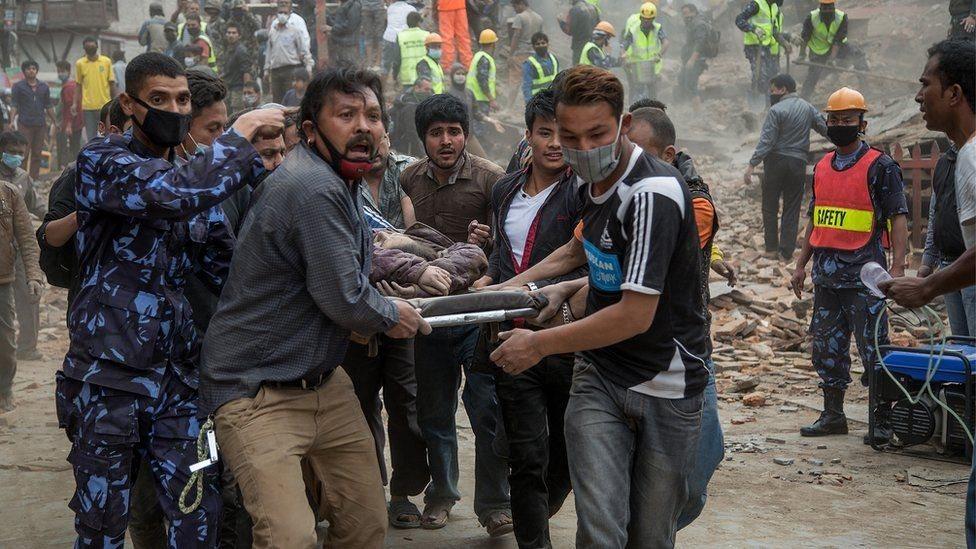 مسعفون يحملون ضحية في أعقاب الزلزال الذي وقع في نيبال في أبريل/نيسان 2015