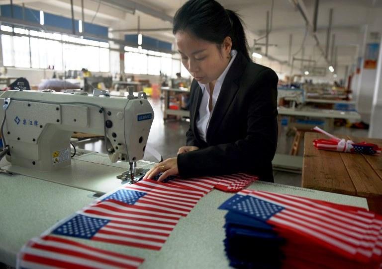 عاملة بمصنع صيني بصدد تحضير أعلام أميركية استعدادا لزيارة ترمب المرتقبة إلى الصين