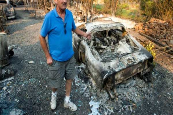 رجل يقف أمام سيارته المحترقة في مقاطعة نابا في ولاية كاليفورنيا