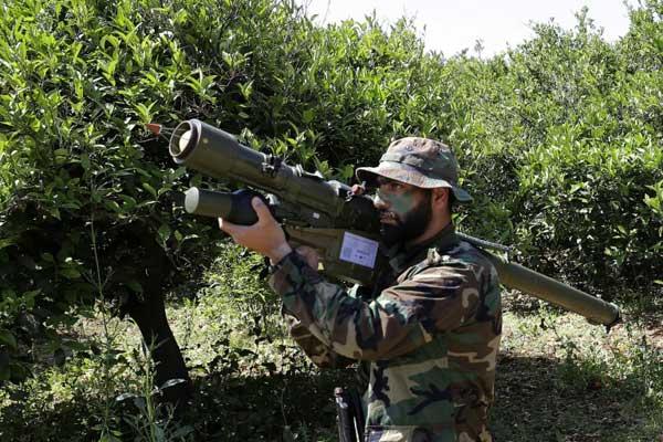 عنصر من حزب الله يحمل على كتفه قاذفة صواريخ في حقل قرب الناقورة في جنوب لبنان على الحدود مع إسرائيل