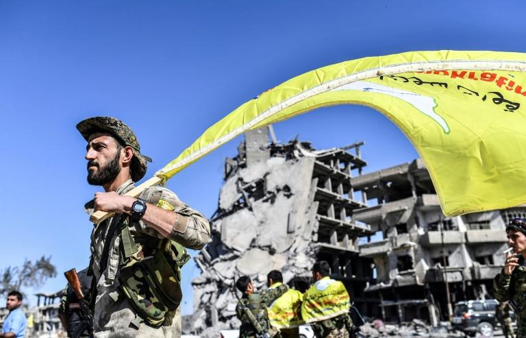 عنصر من قوات سوريا الديموقراطية يرفع علم هذه القوات في الرقة