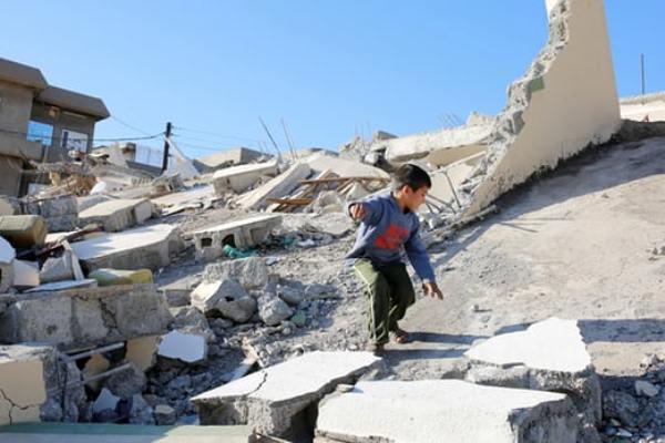 طفل يقف فوق الدمار في السليمانية نتيجة الزلزال الذي ضرب العراق