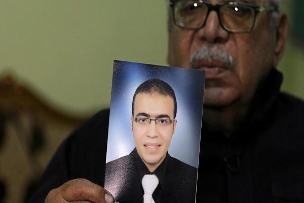 والد المتهم وفي يده صورة لابنه