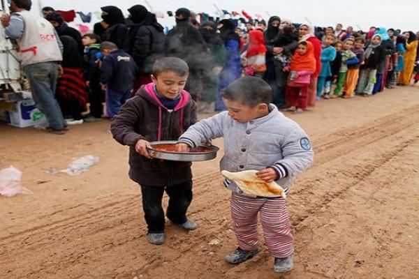 أطفال عراقيون نازحون يتلقون معونات غذائية