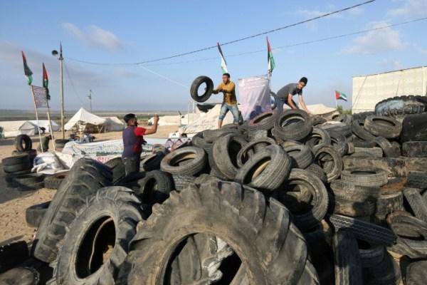 شاب يحضر الاطارات لحرقها مع استعداد الفلسطينيين لتظاهرة على حدود قطاع غزة مع إسرائيل