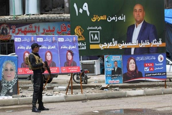 شرطي عراقي يقف أمام صور وشعارات انتخابية