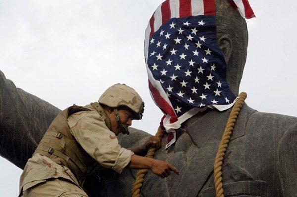جندي أميركي يغطي وجه تمثال صدام حسين بعلم الولايات المتحدة