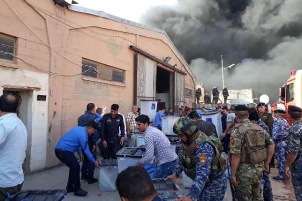 القوات الأمنية العراقية تنقل صناديق الاقتراع من المخازن المحترقة في بغداد