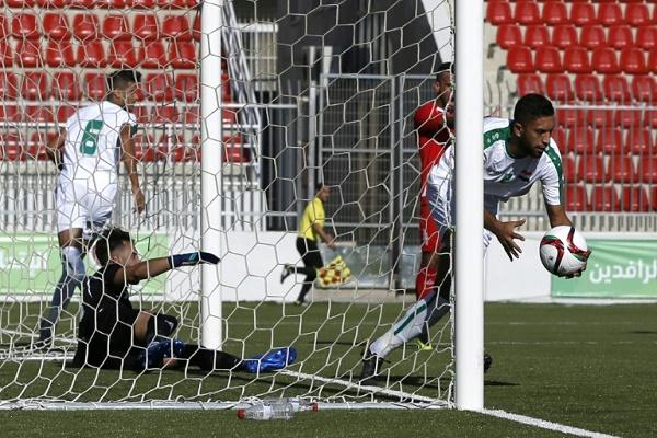 العراقي مصطفى ناظم (يمين) يسجل لبلاده في مرمى فلسطين في مباراة ودية على ملعب فيصل الحسيني في الرام في الضفة الغربية في 4 آب/أغسطس 2018