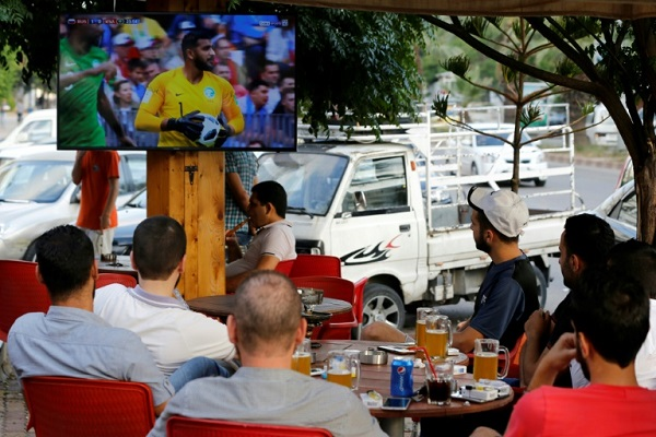 سوريون يشاهدون في مقهى