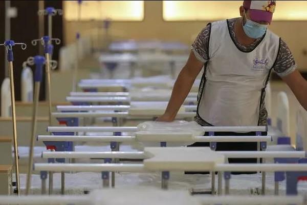 متطوع عراقي يساعد في تجهيز مستشفى ميداني لمرضى كورونا في بغداد