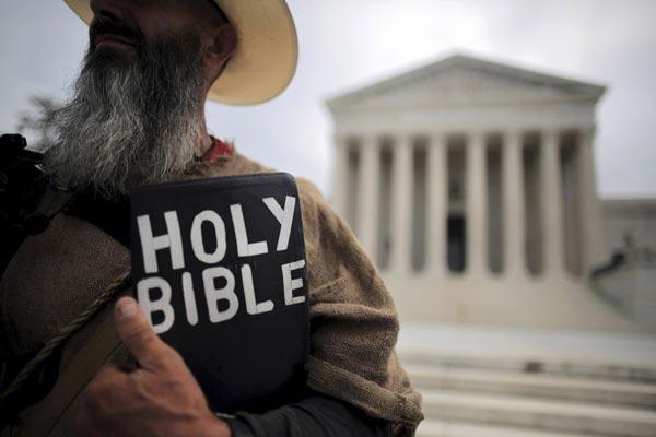 متظاهر يحتج حاملًا إنجيلًا بعدما قضت محكمة في يونيو 2015 بأن إحدى مدن أريزونا انتهكت حقوق حرية التعبير في الكنيسة المحلية من خلال منعها من نشر علامات تخطر الجماهير بخدمات العبادة