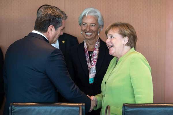 رئيس منظمة التجارة العالمية روبرتو أزيفيدو مصافحًا المستشارة الألمانية في برلين بتاريخ 11 يونيو 2018