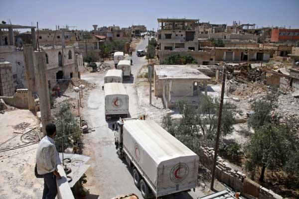 شاحنات تابعة للهلال الأحمر السوري تنقل مساعدات إنسانية عند دخولها إلى مدينة درعا (جنوب) بتاريخ 26 يوليو 2018