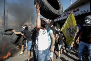 محتجون فلسطينيون يحرقون اطارات في مخيم برج البراجنة للاجئين جنوب بيروت في 16 يوليو 2019