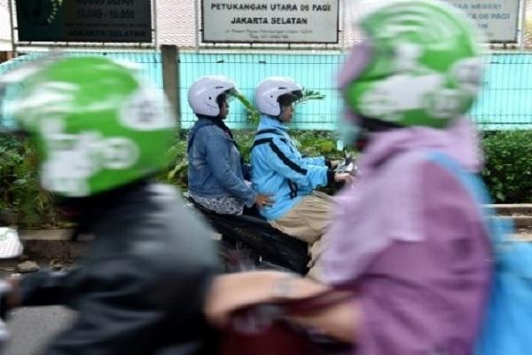 سائقة اجرة على دراجة نارية خلال عملها في اندونيسيا