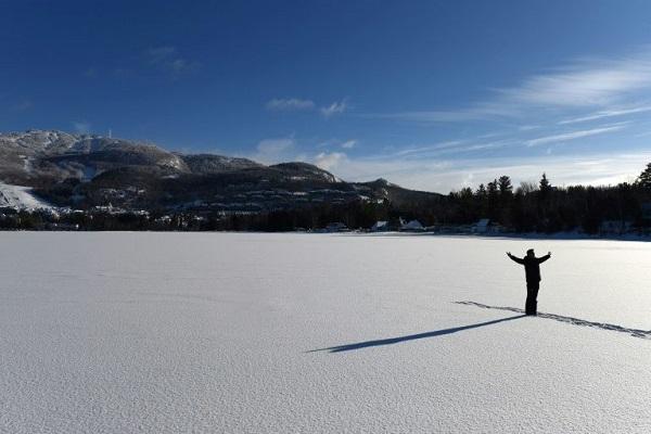 رجل واقف على بحيرة تريمبلان المتجمدة في مقاطعة كيبيك في 24 ديسمبر