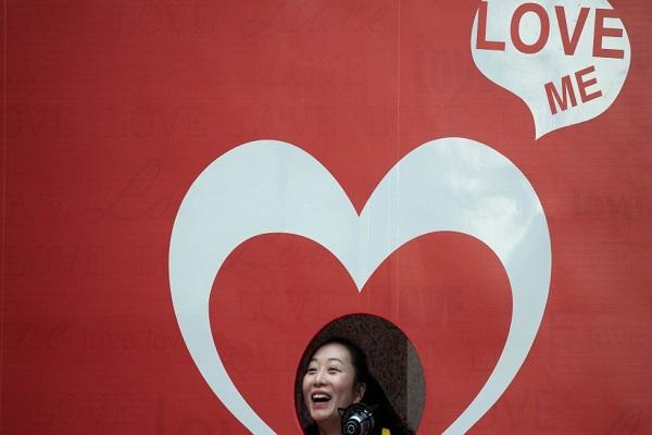 سيدة تلتقط صورة أمام لوحة لمناسبة عيد الحب في هونغ كونغ