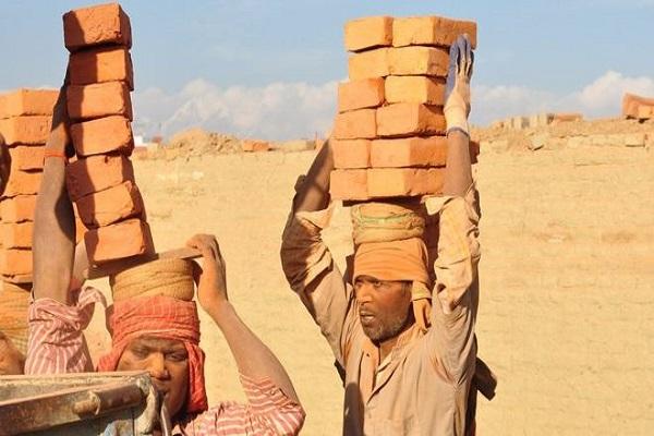 عمال يحملون الطوب في أحد الأفران بعد تطبيق تكنولوجيا جديدة تحد من التلوث