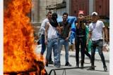 فلسطينيون يحملون حجارة خلف اطارات مشتعلة خلال مواجهة بعد مسيرة احتجاج ضد ورشة البحرين