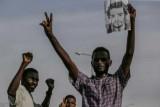 متظاهر سوداني يحمل صورة زميله الذي قتل في فضّ دامٍ لاعتصام أمام مقر قيادة الجيش في العاصمة خلال الشهر الفائت، في مسيرة لتأبين الضحايا في الخرطوم في 13 يوليو 2019