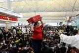 مسافرة تصرخ حاملة حقيبتها أثناء محاولتها الدخول إلى باحة المغادرة في مطار هونغ كونغ الدولي أثناء تظاهرة جديدة في 13 أغسطس 2019