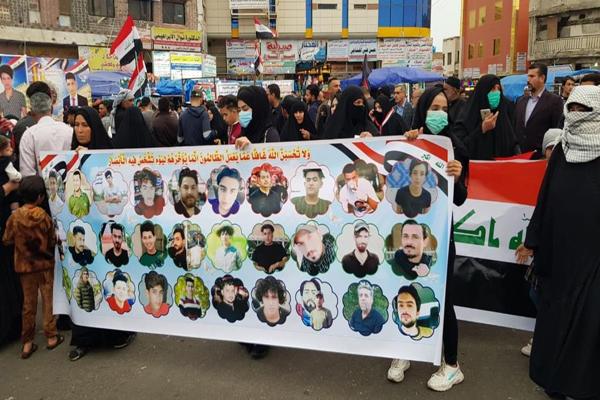 متظاهرون عراقيون يحملون صورًا لناشطين اغتالتهم الميليشيات الموالية لإيران
