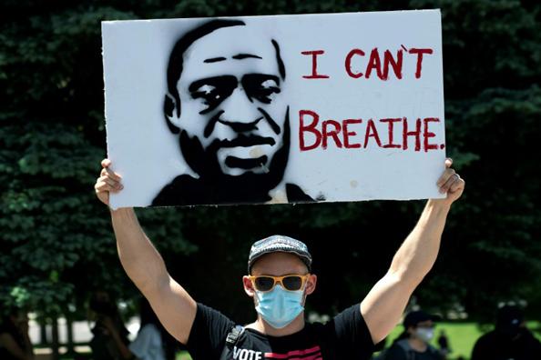 متظاهر يرفع صورة جورج فلويد في دنفر في 30 مايو 2020