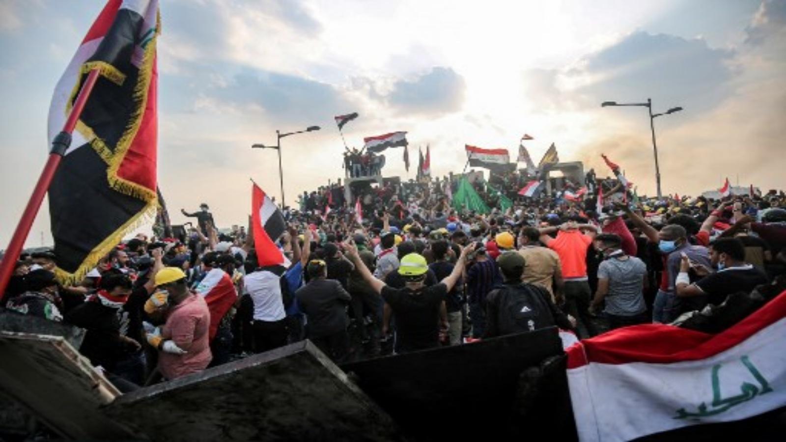 هذه الصورة التي التقطت في 29 أكتوبر / تشرين الأول 2019 ، المتظاهرون العراقيون يلوحون بالأعلام الوطنية وهم يقفون فوق حواجز خرسانية عبر جسر الجمهورية في العاصمة بغداد الذي يربط بين ساحة التحرير والمنطقة الخضراء شديدة الحراسة. أ ف ب