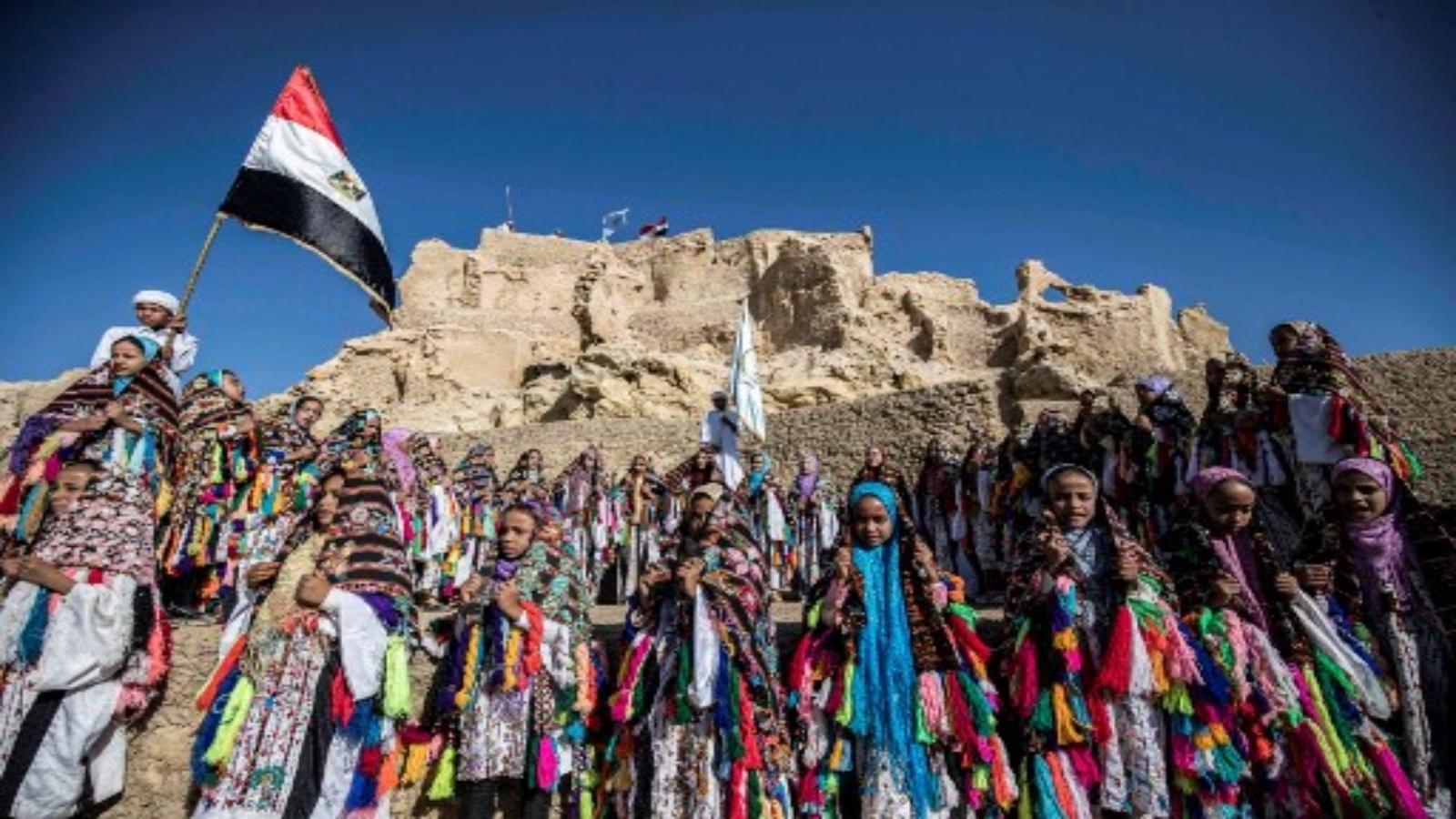أطفال مدارس يرتدون ملابس تقليدية يجتمعون خلال احتفال بمناسبة افتتاح حصن شالي بعد ترميمه في واحة سيوة الصحراوية في مصرعلى بعد 600 كيلومتر جنوب غرب العاصمة القاهرة في 6 نوفمبر 2020.