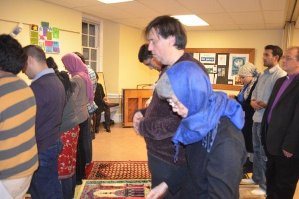 رجال ونساء يصلون جنباً إلى جنب خلف إمام دعي