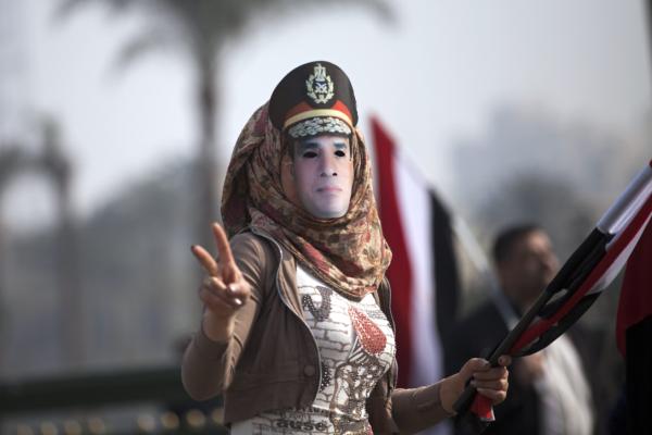 مصرية تغطي وجهها بصورة السيسي في ميدان التحرير