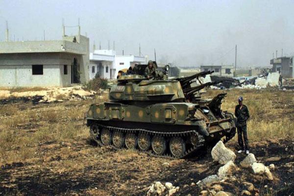 جندي سوري يقف بالقرب من دبابة تابعة للنظام