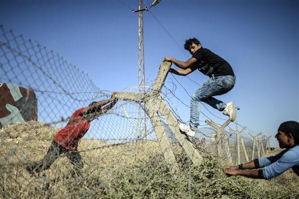 متظاهرون أكراد يحاولون هدم جدار حدودي للعبور إلى سوريا
