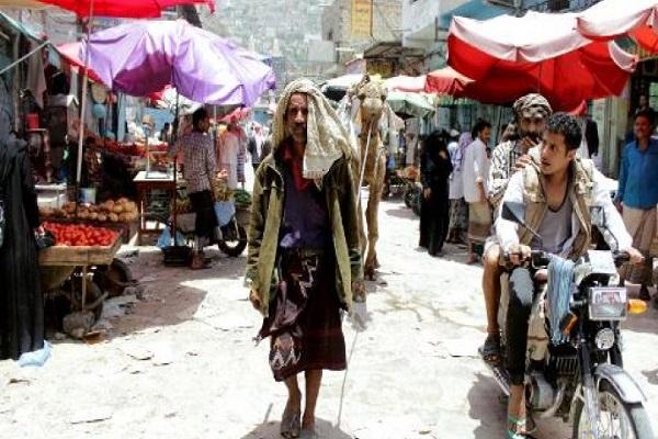 يمني يسير مع جمله في احد اسواق جنوب غرب تعز
