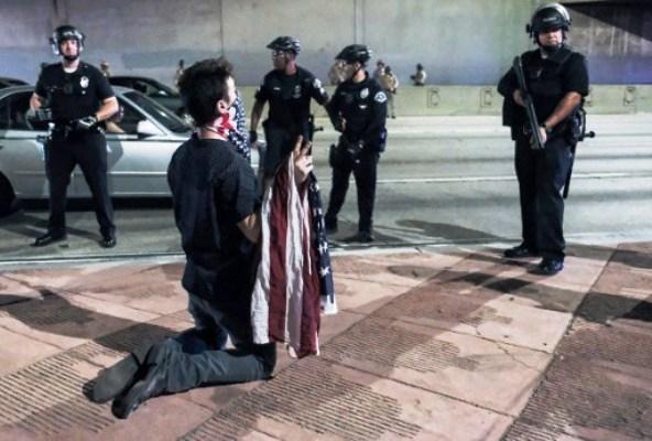 محتج أميركي على فوز ترامب محاطا بعدد من عناصر الشرطة