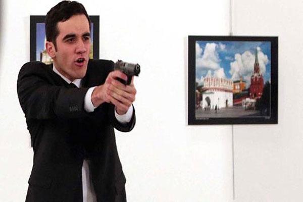 الشرطي القاتل موجّهًا مسدسه نحو السفير الروسي