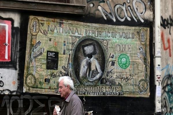 رجل يمر بجانب لوحات على الجدار في اثينا