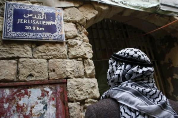 فلسطيني أمام لوحة تشير الى طريق القدس - Jerusalem