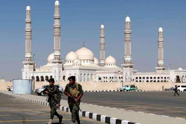 مسلحان من عناصر الحوثي أمام مسجد الصالح