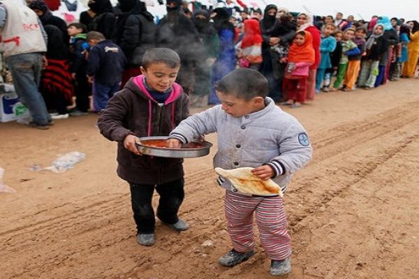 اطفال نازحون يتقاسمون المعونات الغذائية