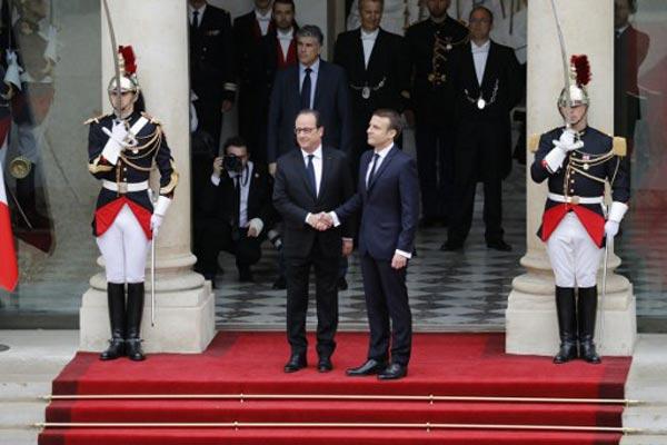 مصافحة بين رئيس فرنسا السابق والحالي عند مدخل الإليزيه