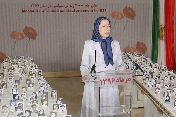 رجوي مع مجموعة من صور ضحايا مجزرة 1988 باعدام 30 الف سجين سياسي
