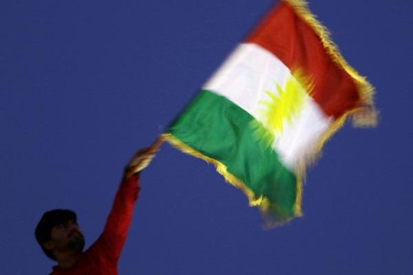 رجل يلوح بالعلم الكردي خلال تجمع تأييد للاستفتاء في أربيل
