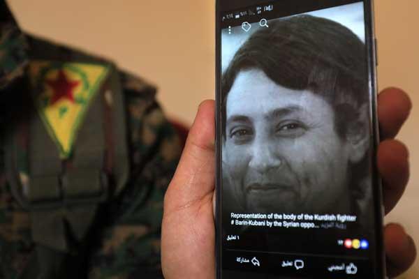 صورة المقاتلة الكردية التي جرى التمثيل بجثتها تندو على هاتف خلوي