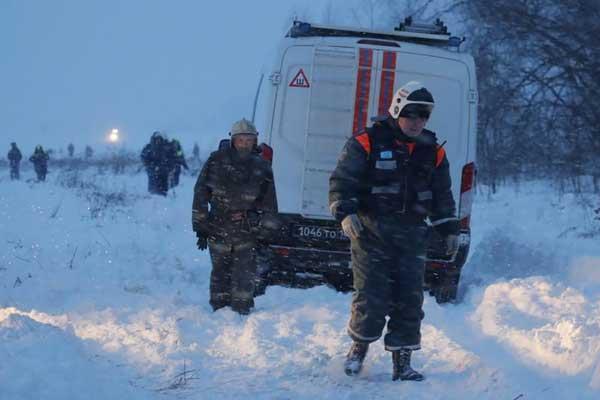 عمال في خدمات الطوارئ في موقع سقوط طائرة روسية قرب موسكو يوم الاحد