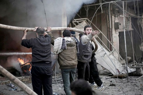 أشخاص يحاولون إخماد نيران اشتعلت على إثر غارات جوية في الغوطة الشرقية