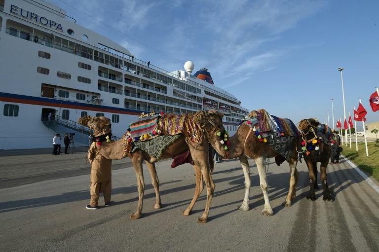 تونسي بانتظار الزبائن لنقلهم بواسطة الجمال امام السفينة السياحية الالمانية