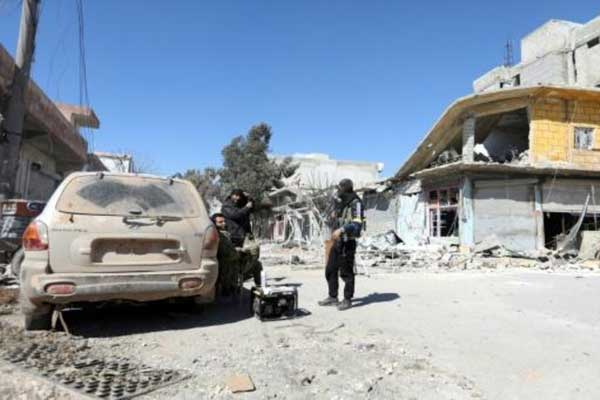مقاتلان من الفصائل السورية الموالية لتركيا عند حاجز في بلدة جنديرس في منطقة عفرين