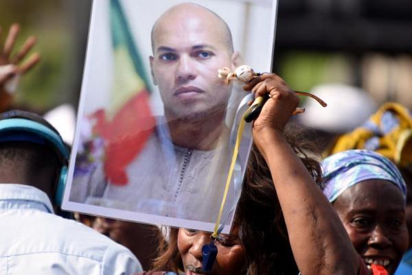 أنصار كريم واد يحملون صورته